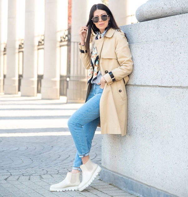 Influencer with beige trench coat leaning against concrete wall wearing Cougar Firenze Rain Boots in Oyster