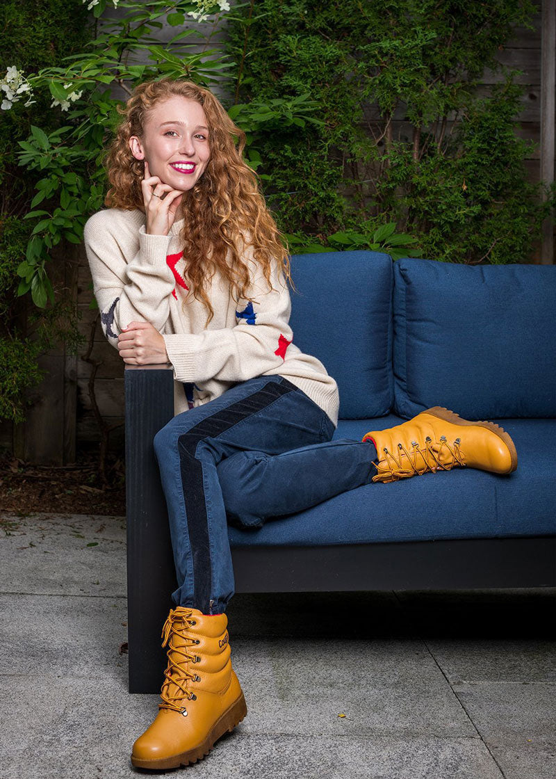 Influencer with long red hair sitting on blue couch wearing Cougar Original Pillow Boot in Tan