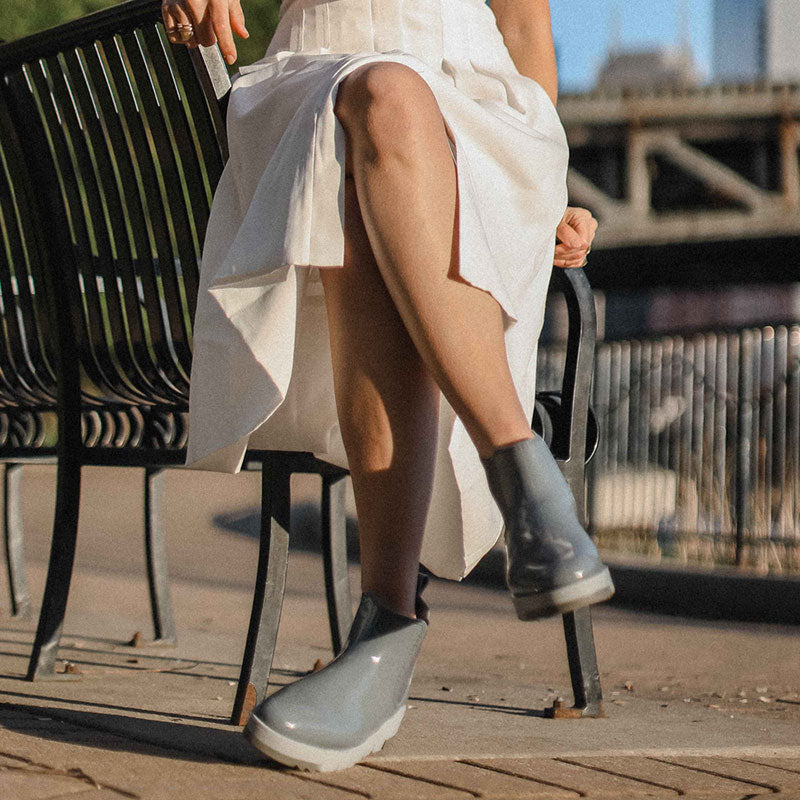 Influencer in white dress sitting with legs crossed wearing Cougar Firenze Rain Boots in Ash Blue