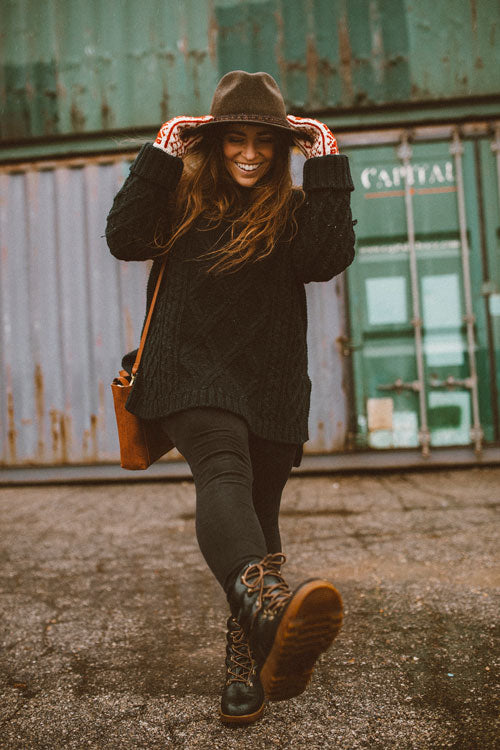Influencer wearing black sweater, jeans and holding black hat walking outside wearing Cougar Original Pillow Boot in Black