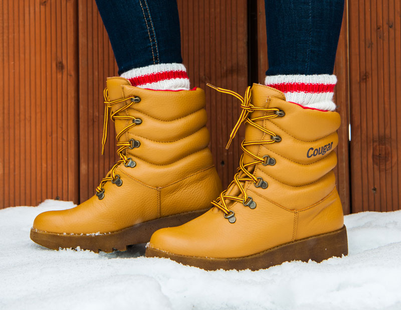 Christine Carlton wearing Cougar Original Piillow Boots in Tan in dark blue jeans and wool socks in snow