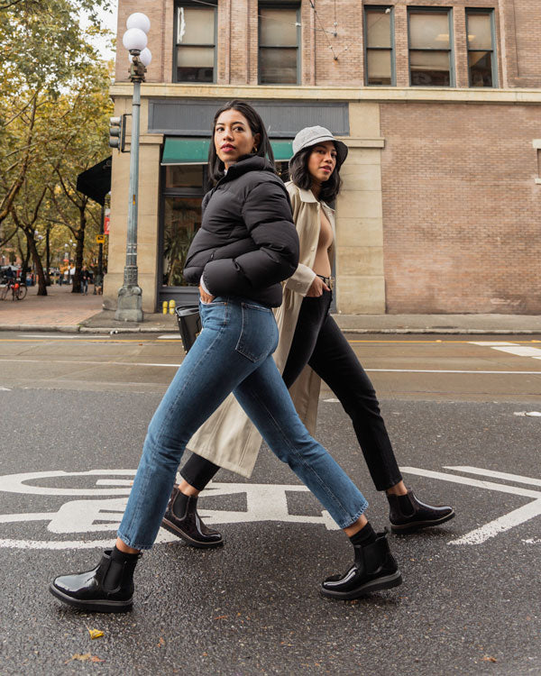 Identical twins Kathleen and Kim on city street walking in opposite directions wearing Cougar Kensington Chelsea Rain Boots