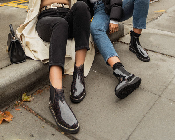 Identical twins Kathleen and Kim sitting on city street curb wearing Cougar Kensington Chelsea Rain Boots