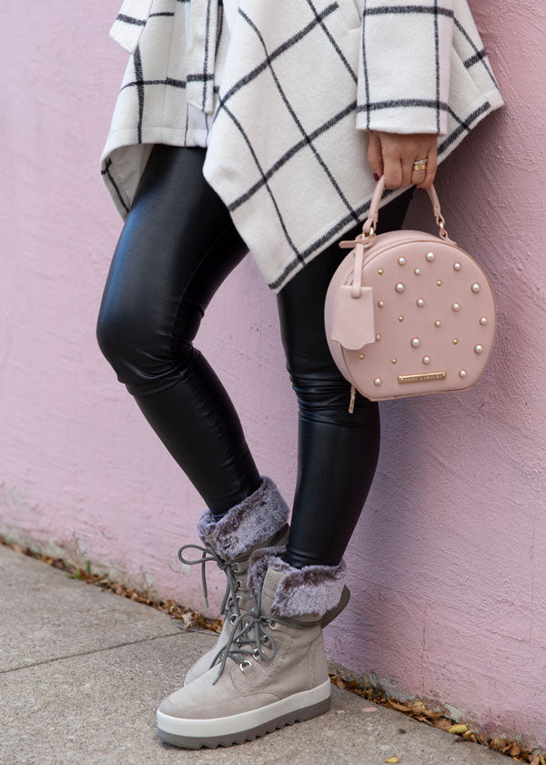Krystin Lee leaning on pink concrete wall holding pink purse  and Vanetta Suede Mid Boot in Mushroom