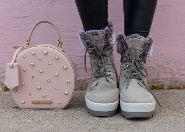 Krystin Lee feet Vanetta Suede Mid Boot in Mushroom and pink purse next to feet
