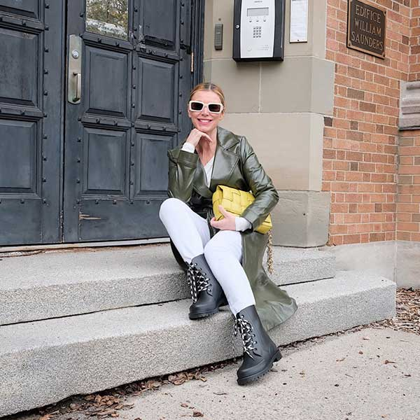 Influencer in olive jacket, yellow clutch sitting on townhouse stoop wearing Cougar Madrid Rain Boots in Black