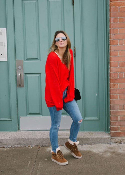 Influencer standing in front of teal door outside wearing bright red shirt, blue jeans and Cougar Daniel Winter Sneaker in Draft