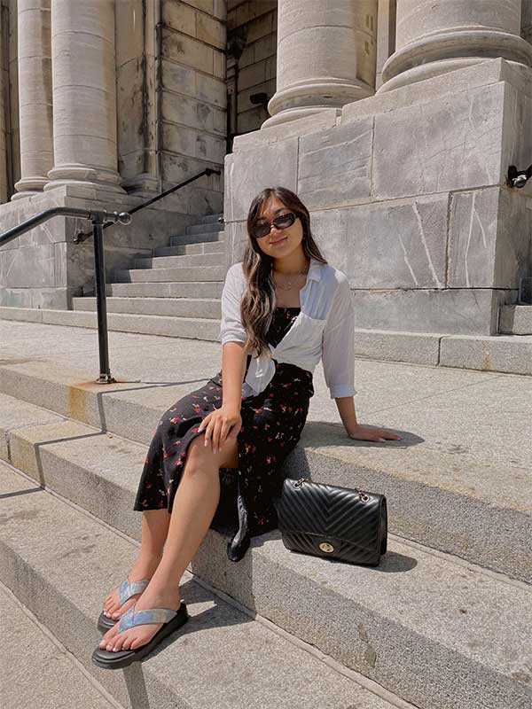 Influencer sitting outside on concrete stairs in dress and sunglasses wearing Cougar Jacy Sandals in Opal