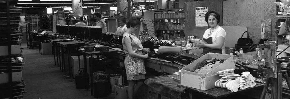 Women working along assembly line in shoe manufacturing plant.