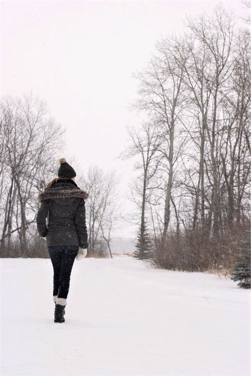 Regan Wiebe walking outside in snow wearing jacket, hat mits and Cougar Blackout Leather Winter Boot