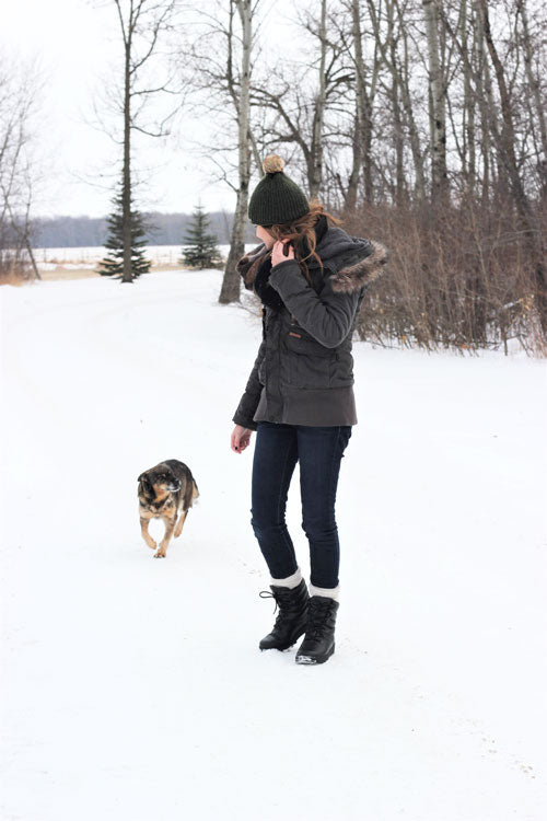 Regan Wiebe walking outside in snow with dog wearing jacket, hat mits and Cougar Blackout Leather Winter Boot
