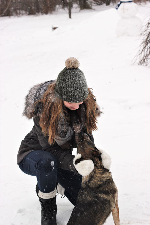 Regan Wiebe kneeling in snow to pet dog wearing jacket, hat mits and Cougar Blackout Leather Winter Boot