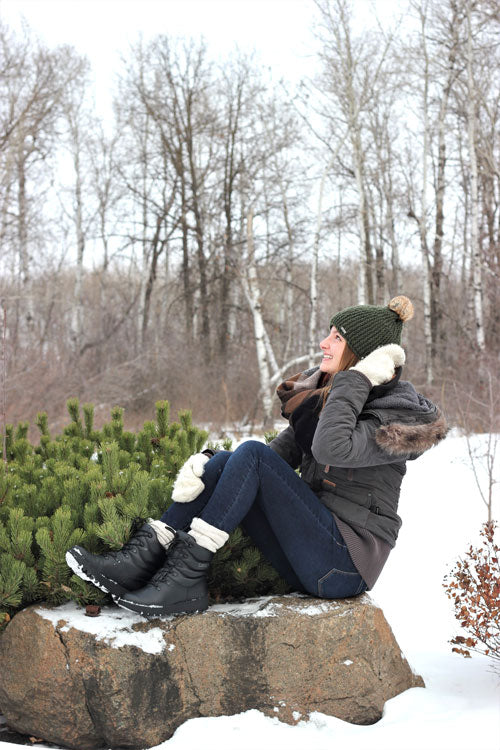 Regan Wiebe sitting on rock outside in snow wearing jacket, hat mits and Cougar Blackout Leather Winter Boot