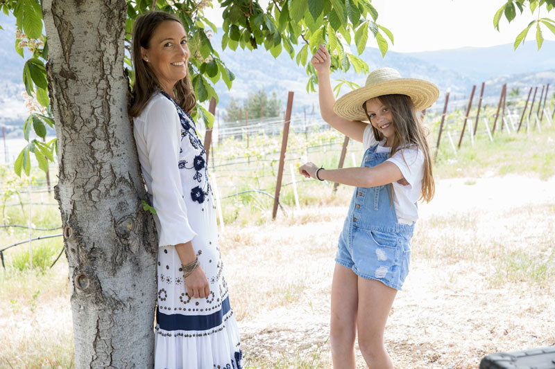 Sarah Bancroft leaning against tree in Birch Block Vineyard with her daughter
