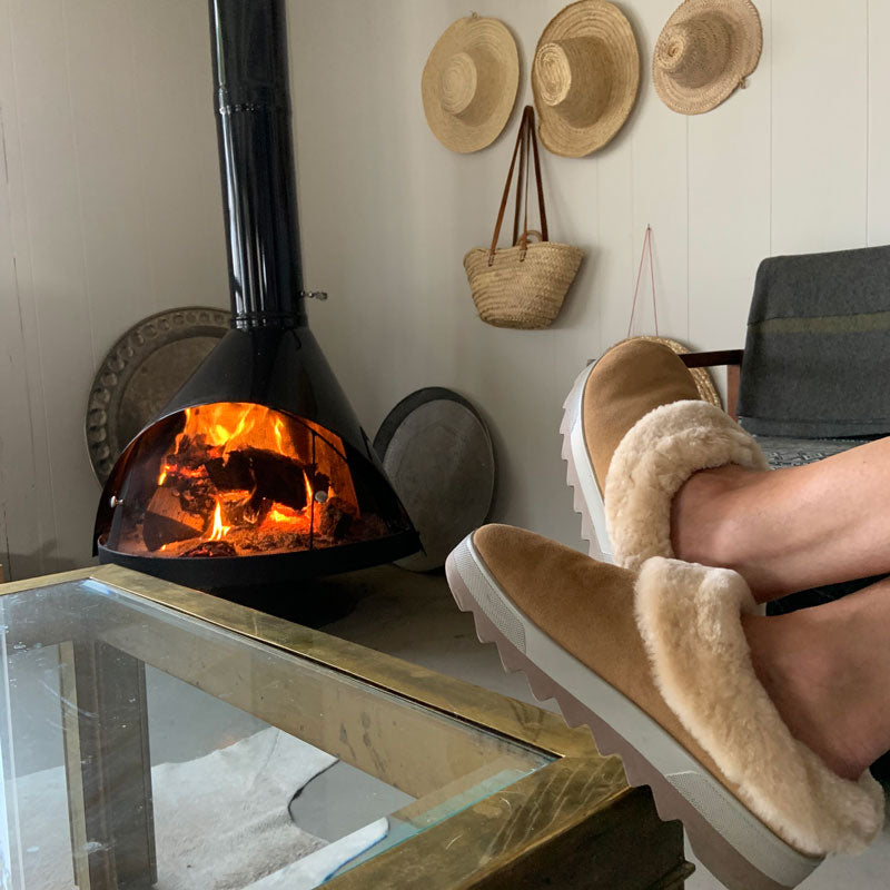 Feet up on coffee table next to fire wearing Cougar Pronya Shearling Mule in Tan