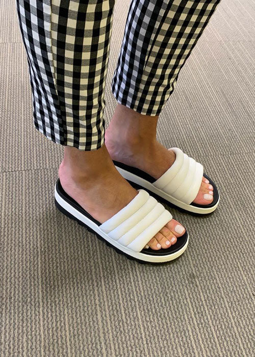 Sarah Bancrofts feet wearing black and white checkered pants with Cougar Prato Leather Sandals in White