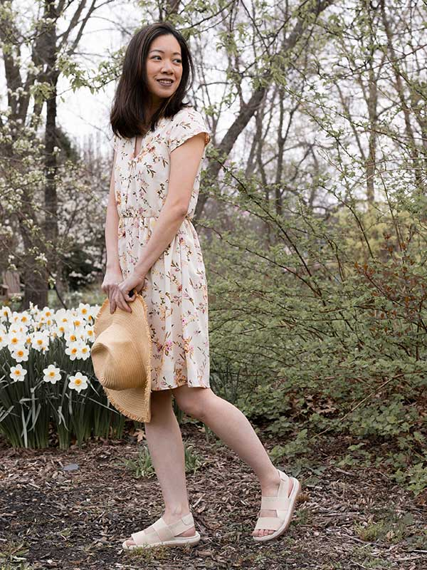 Influencer in forest in summer dress holding straw hat wearing Cougar Luscia Elastic Sandal in Oyster-Gold