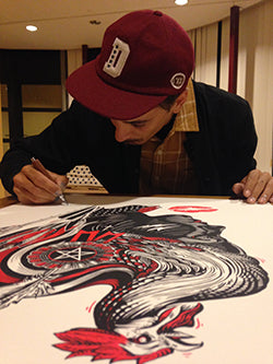 Dourone signing the artwork