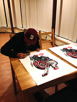 Dourone signing his artwork