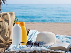 There are sun products including sunscreen and aftersun on a beach.