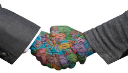 Two hands shaking hands with map of world painted on hands.