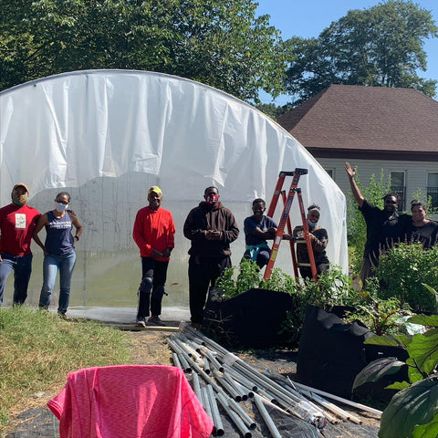 Sunny day photo of 8 volunteers standing in front of plastic-covered hoop house on the farm.