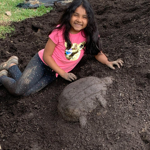 Brown girl with long black hair reclining on a hill of soil near a turtle sculpture she made out of soil.