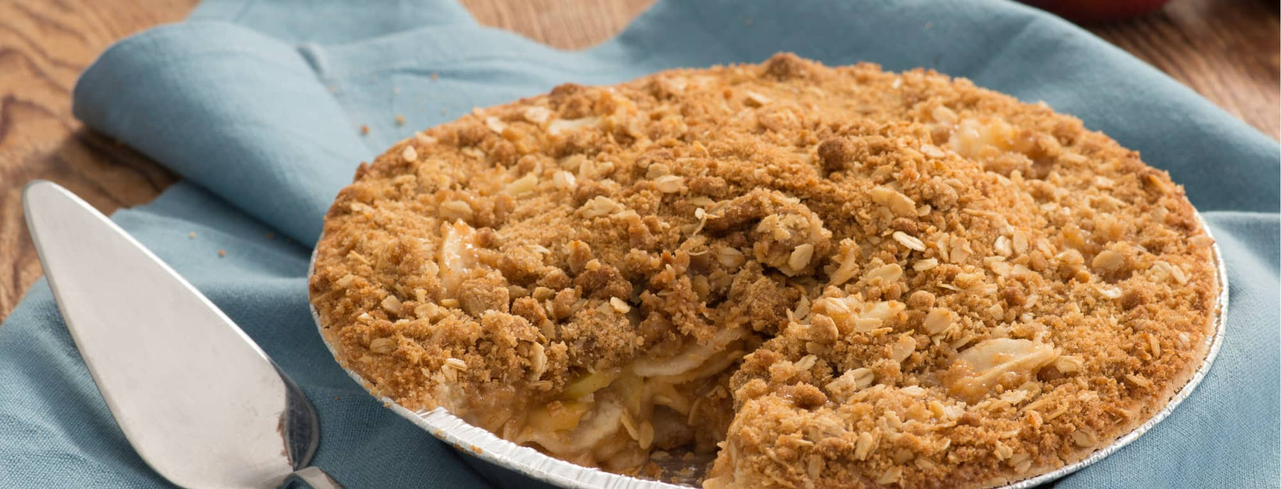 Apple crumble pie, with one slice cut out. The pie tin is on a blue napkin, with a pie serving tool next to it