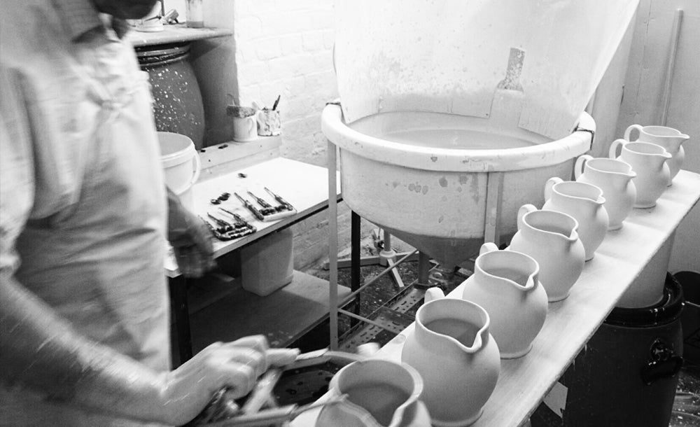 Dipping ceramic jugs into a pool of glaze
