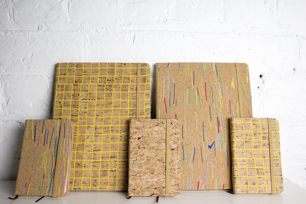 Collection of cork note books in yellow and colour patterns over the cork