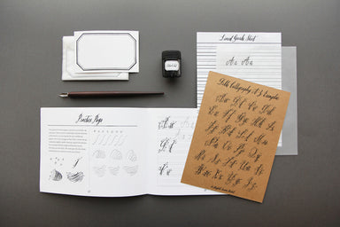 The Belle Calligraphy kit includes a dip pen, instruction booklet, practice paper, decorative notes, and black ink bottle.