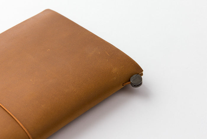 The Camel Midori Traveler's Notebook Regular features a metal closure to keep the elastic in place.