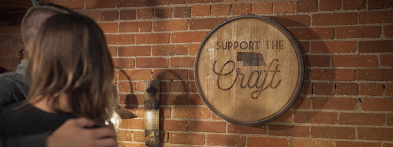"""Couple looking at barrel head with """"Support the Craft"""" and state of Nebraska on front hanging on brick wall."""
