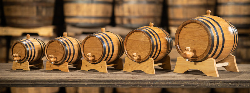 Different sizes of oak aging barrels in warehouse of other barrels