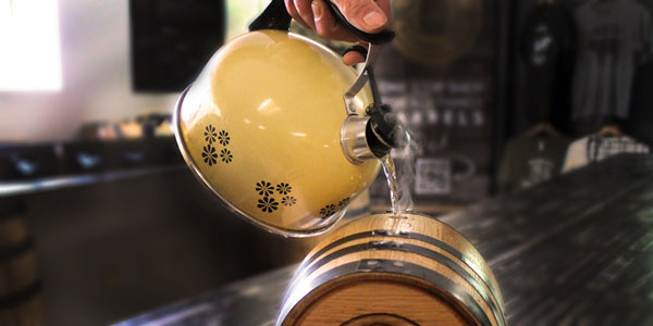 Filling oak aging barrel with hot water from a kettle to swell