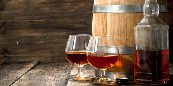 Whiskey in glasses next to bottle and barrel