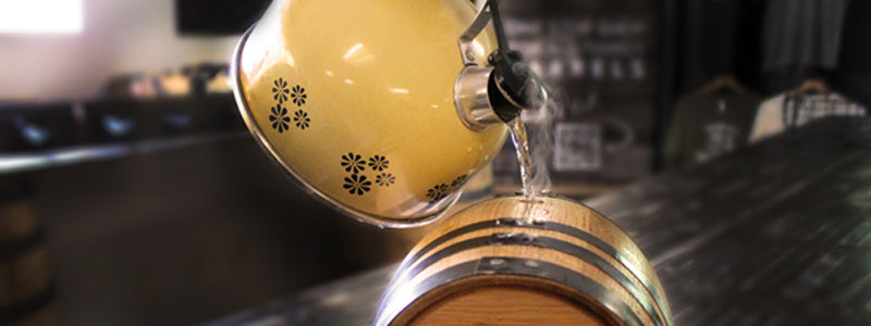 Filling oak aging barrel with hot water from kettle to swell