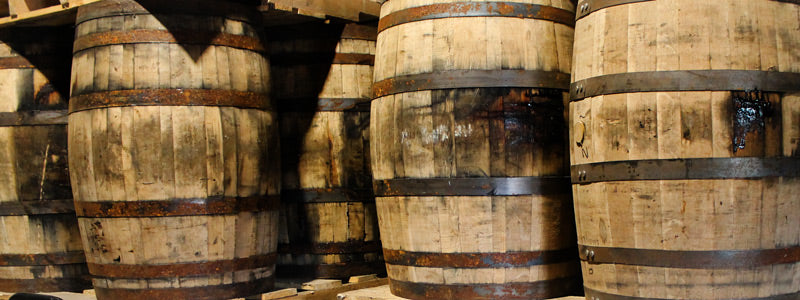 Whiskey barrels stacked on pallets in warehouse