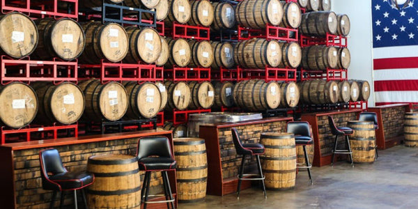 Barrels on racks and seats nearby at Revolution Brewing