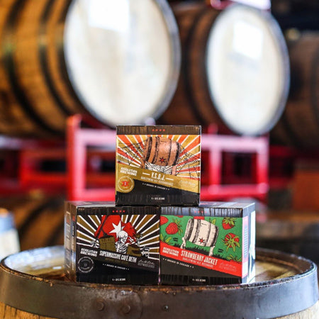 4-pack boxes of VSOJ, Supermassive Cafe Deth and Strawberry Jacket from Revolution Brewing on a barrel head.