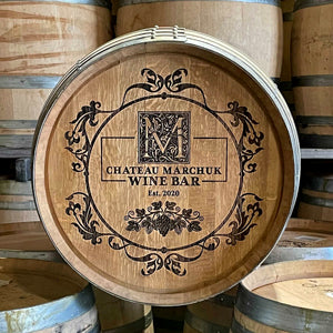 """Laser engraved full-size barrel with text """"Chateau Marchuk Wine Bar"""" and a circular floral/vine design"""