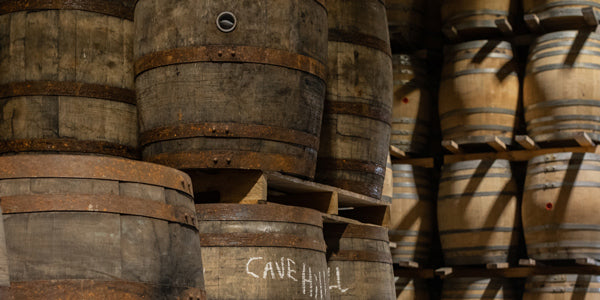Whiskey barrels stacked on pallets in a warehouse