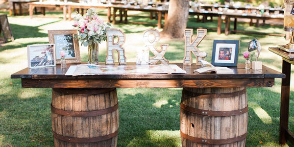 Wood slab table at wedding using barrels as supports