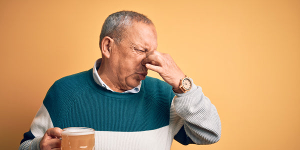 Man plugging his nose after sniffing the beer he is holding.