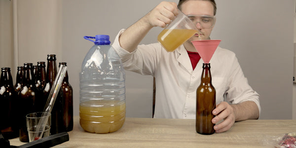 Homebrewer pouring beer from larger container into glass bottles