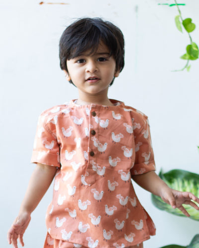 A 2 year old wearing a soft peach color summer dress
