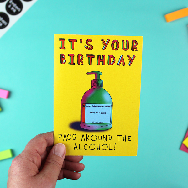 A hand holds a portrait orientated birthday card with a yellow background and a colourful illustration of a hand sanitizer, and the words 'it's your birthday, pass around the alcohol'!