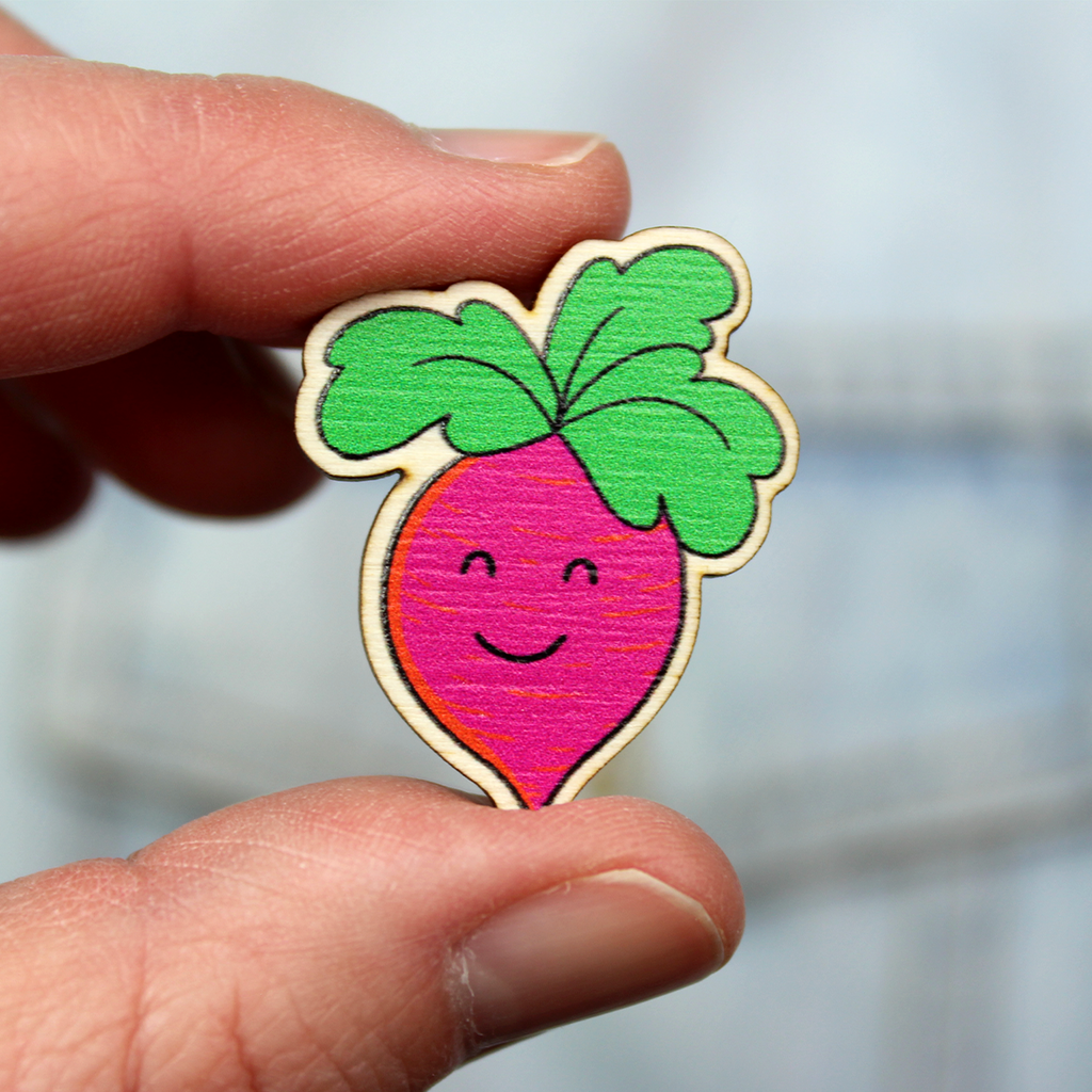 A wooden badge of a pink root vegetable with a smiling face and green leaf hair is held between finger and thumb in front of a denim jacket.