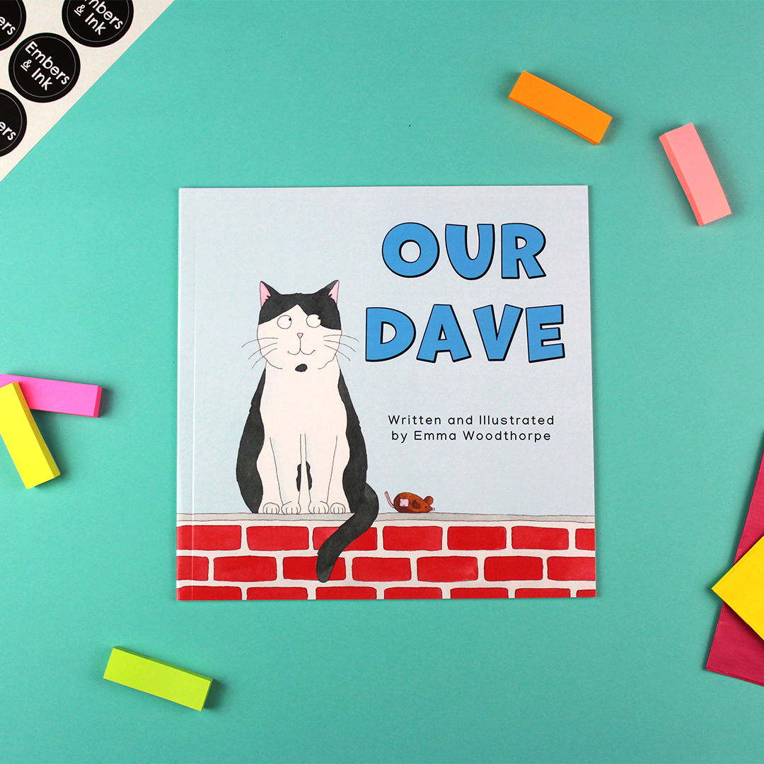 A children's book called Our Dave by Emma Woodthorpe is laying on a colourful table. The front cover shows an illustration of a black and white cat sitting on a wall next to a toy mouse.