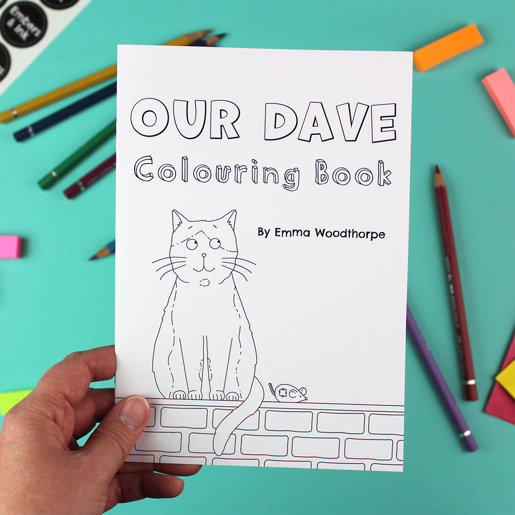 A hand holds the Our Dave Colouring Book by Emma Woodthorpe. It includes an illustration of a cat sitting on a wall, next to a toy mouse. It is all black and shite and ready to be coloured in.